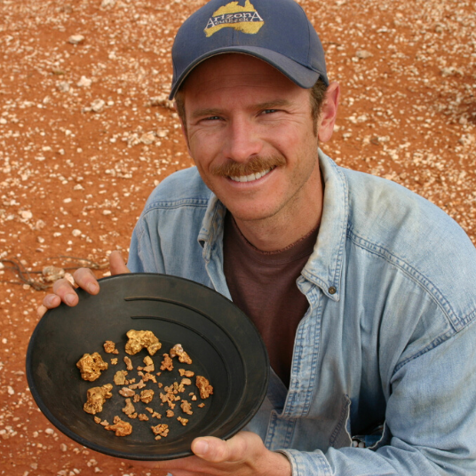 Man smiling with gold nuggets in pan